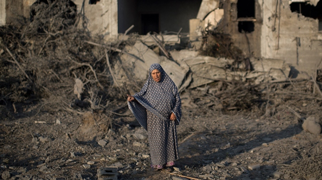 A Palestinian woman gestures as she stands amidst destruction following an Israeli military strike in Gaza City on July 08, 2014 (AFP Photo / Mahmud Hams)