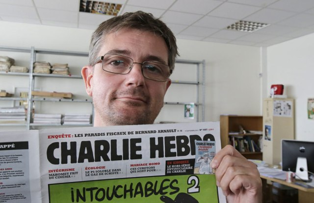 In this Sept.19, 2012 file photo, publishing director of the satirical weekly Charlie Hebdo Stéphane Charbonnier - also known as Charb - displays the front page of the newspaper as he poses for photographers in Paris. Masked gunmen stormed the Paris offices of Charlie Hebdo Wednesday Jan.7, 2015, killing 12 people including Charb, before escaping.